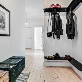 Угловая полочка черного цвета в прихожей под вешалкой
