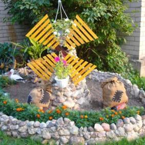Декоративная мельница на клумбе из камня