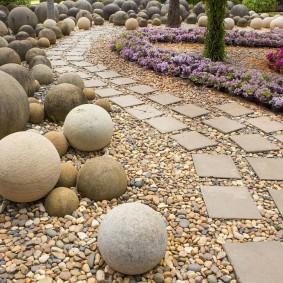 Круглые камни вдоль тропинки из бетонной плитки