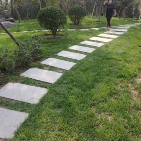 Бетонная дорожка из плиток через зеленый газон