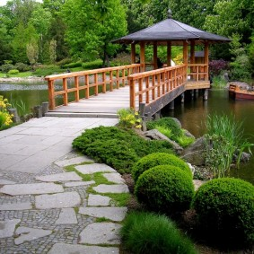 Деревянный мост к беседке посередине водоема
