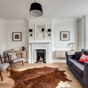 Серый диван в гостиной с белыми стенами