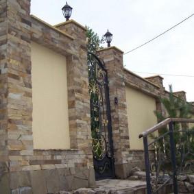 Кованная калитка на столбах с каменной отделкой