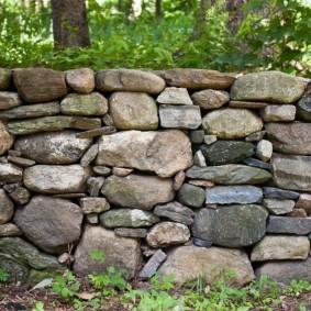 Невысокий забор из камня разного размера