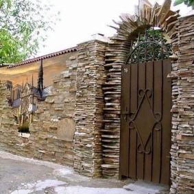 Каменная арка над металлической калиткой