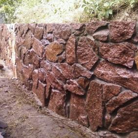 Каменный забор с лакированной поверхностью