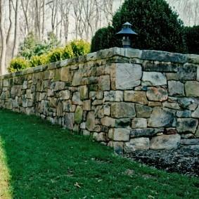 Массивная стенка из камня на садовом участке