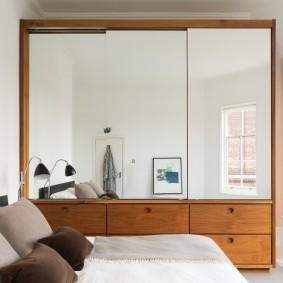 Зеркальные дверцы шкафа в спальной комнате