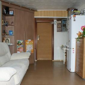 Белый холодильник напротив раскладного дивана