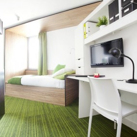 Зеленый ковер в полоску на полу комнаты
