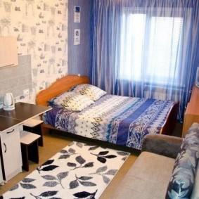Широкая кровать перед окном небольшой комнаты