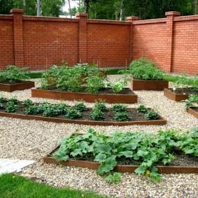 Кирпичный забор на загородном участке с огородом