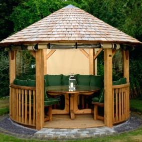 Деревянный столик внутри небольшой беседки
