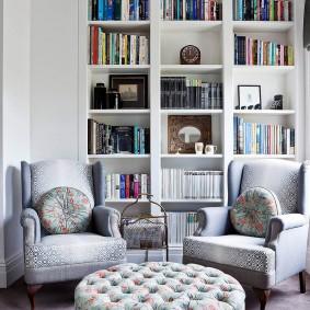 Книжный стеллаж за креслами в комнате