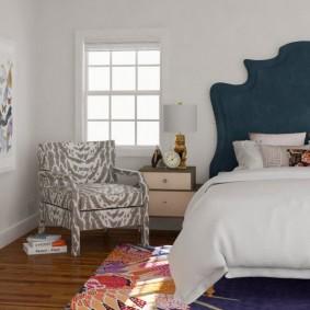 Небольшое кресло в комнате с кроватью
