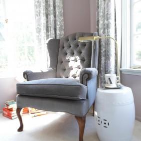 Светло-серое кресло на фигурных ножках