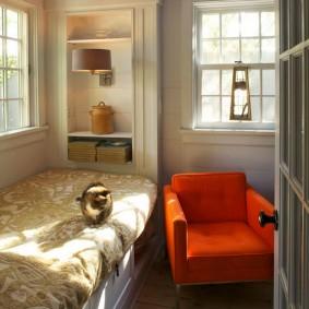 Небольшое кресло рядом с кроватью-диваном