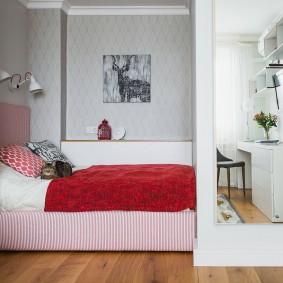 Красное одеяло на кровати в нише