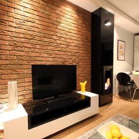 Черно-белая тумба для размещения телевизора в кухне-гостиной