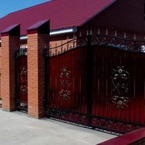 Кованные ворота с поликарбонатом на кирпичных колоннах