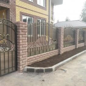 Клумба с бетонным бордюром перед кирпичным забором