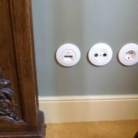 Круглые розетки в нижней части стены спальни