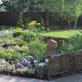 Садовая клумба с плетенными бортиками
