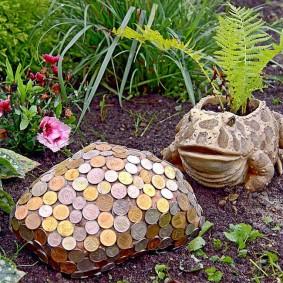 Садовая черепаха из монет на цветочной клумбе