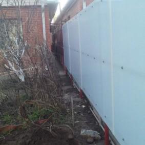 Высокий забор из листов асбестоцементного шифера