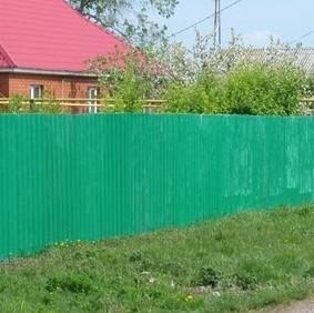 Зеленый забор перед деревенским домом