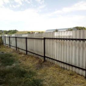 Металлические прожилины на заборе из шифера