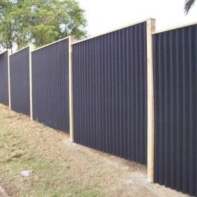 Забор из волнистых листов на участке с рельефом