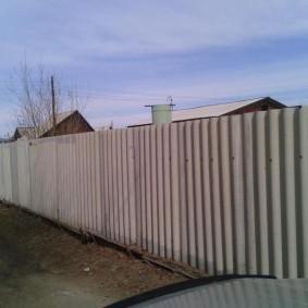 Волнистый шифер на заборе дачного участка