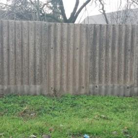 Старые листы шифера на ограде дачного участка