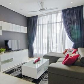 Белая мебель в гостиной с серой стеной