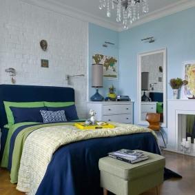 Синяя кровать в спальне с камином