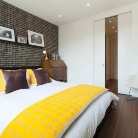 Желтое одеяло на кровати в спальне