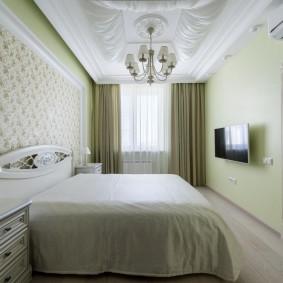 Узкая спальня с телевизором на стене