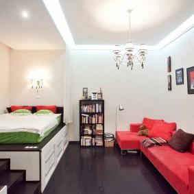 Красный диван в комнате с кроватью на подиуме