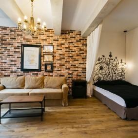 Интерьер спальни-гостиной с обоями под кирпич