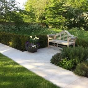 Деревянная скамейка в саду с бетонными дорожками