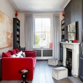 Красный диван в маленькой гостиной с камином