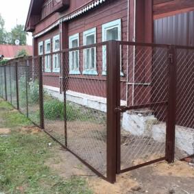Высокий забор из сетки рабицы на стальном каркасе