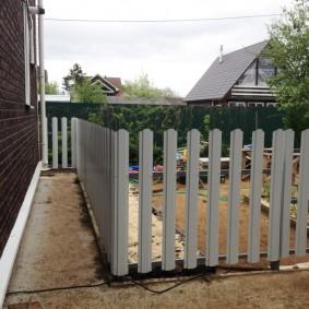 Металлический штакетник на заборе у дома