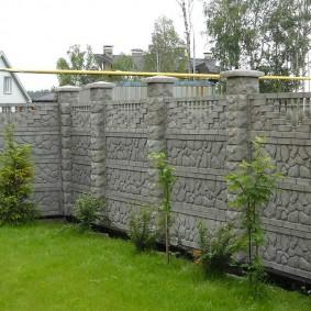 Зеленый газон на участке с железобетонным забором