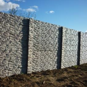 Глухой забор из бетона с отделкой камнем