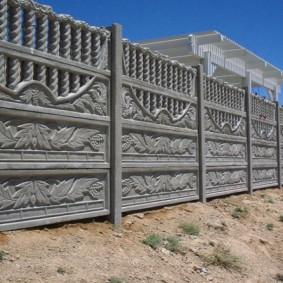 Рельеф в форме листьев на железобетонном заборе