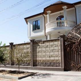 Красивые кованные ворота перед двухэтажным домом