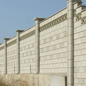 Высокая ограда из бетонных блоков
