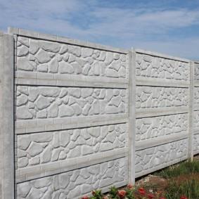 Каменная фактура на поверхности бетонной ограды
